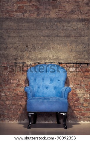 An antique blue velvet chair near the grungy brick wall