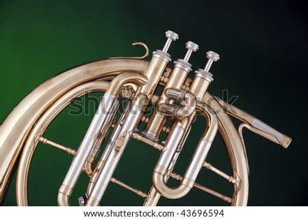 An antique brass peckhorn or French horn isolated against a spotlight green background.