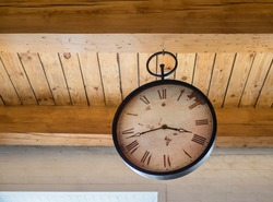 An antique clock with a large dial hangs on a wooden ceiling.