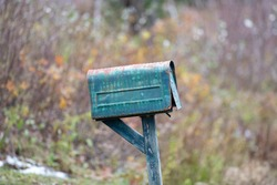 An antique country style green metal mailbox with the door open on a grey wooden post on a roadside. The letterbox is tilted off balance. There are yellow, orange and green shrubs in the background