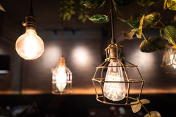 An antique design lighting bulb/chandelier with metal rusty cage that hanging for room interior decoration. Selective focus on one lighting lamp.