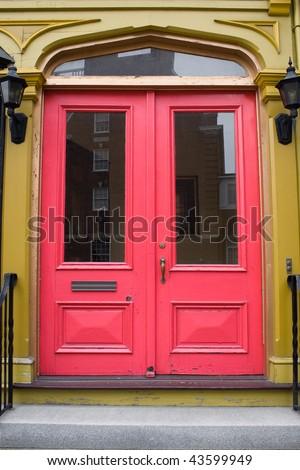 An antique doorway with red painted doors.
