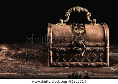 An antique engraved wooden jewelry box in the form of a treasure chest