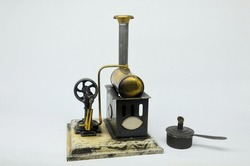 An antique Ernst Plank toy stationary steam engine on a plain background.