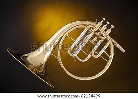 An antique French horn or peckhorn isolated against a spotlight yellow background with copy space.