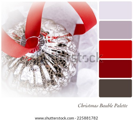 An antique glass Christmas tree decoration, on a red ribbon, and nestled in tissue paper wrapping. In a colour palette with complimentary colour swatches.