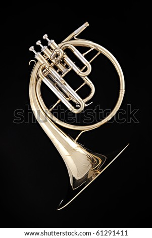 An antique gold French horn isolated against a black background.