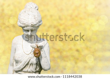 An antique gold medallion will presented from stone statue woman in front of yellow bokeh background. Useful for advertising for gold and antique trade. #1118442038