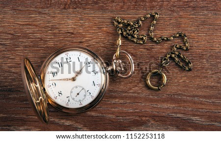 An antique gold pocket watch lies on a wooden table top view  Foto d'archivio ©