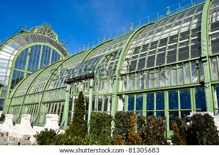 an antique greenhouse with aged steel under a clear blue sky
