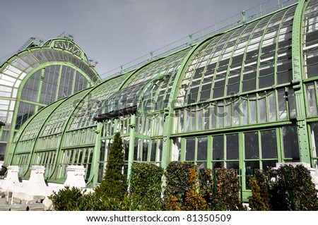 an antique greenhouse with aged steel under a grey overcast sky