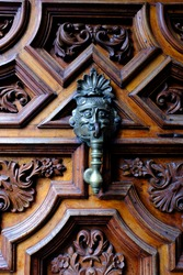 An antique metal door knocker on a carved wooden door at Casa Alvardo or the National Sound Archive (Fonoteca Nacional) with unique architecture in Coyoacán, Mexico City, Mexico.