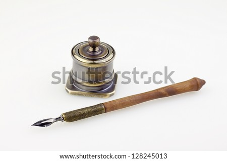 An antique metallic inkwell and old pen isolated background