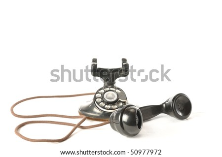 An antique telephone with handset off the hook - stock photo
