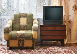 An antique TV stands on an old wooden cabinet, antique design in a 1980s and 1990s style home. Interior in the style of the USSR.