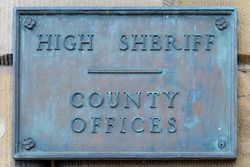 An antique weathered copper or brass sign with raised letters that say HIGH SHERIFF COUNTY OFFICES. The sign is on a building and tarnished with age..