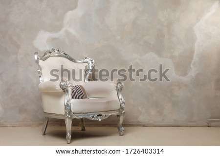 An antique white chair against the wall. Antique leather chair. There is a striped pillow on the chair