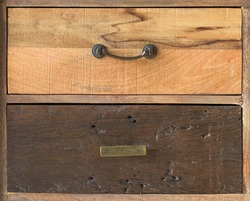 An antique wooden chest of drawers with metal handles, different kind old wooden boxes