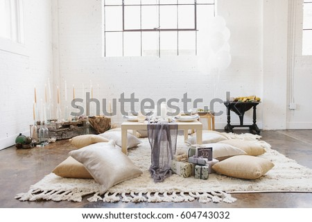 An apartment with a table set for a celebration meal Cushions on the floor