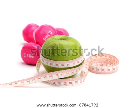 An apple, a measuring tape and dunbbell isolated on white background