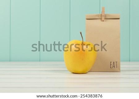 An apple and a paper bag with lunch on a white wooden table with a robin egg blue wainscot. Vintage Style.