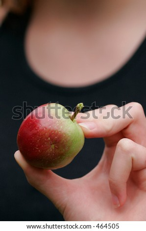 An apple in the hand of a girl