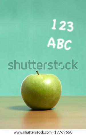 An apple on a teachers desk in the classroom with abc\'s