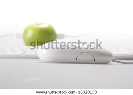 An apple on desktop white keyboard and mouse on white background