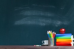 An apple on rainbow colored books in classroom. Back to school concept