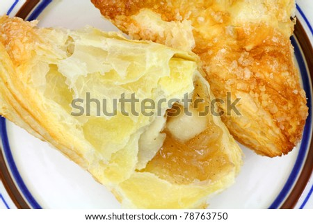 An apple turnover that has been opened to show the fruit and filling on a striped plate.