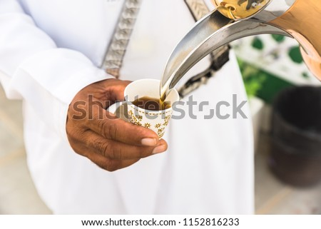 An Arab man in white Kandura serving/Pouring arabic coffee to a disposable paper cup from a traditional teapot/kettle called Dallah in U.A.E.