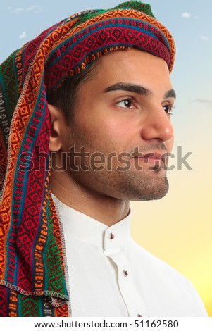 An arab middle eastern man looks out expectantly, earnestly.  He is wearing traditional clothing