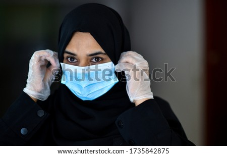 An arab woman wears an face mask respirator while leaning on a shopping cart outside of a Supermarket. The woman is protecting herself from coronavirus and other airborne particles and diseases.