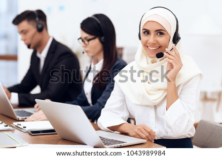 An Arab woman works in a call center. She\'s an operator. Her colleagues work nearby.