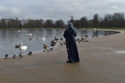 An Arabic woman with a hijab head scarf walking by the round pond among common British waterbirds Mute swans Canada and Egyptian geese pigeons in an English park readily accessible by public transport