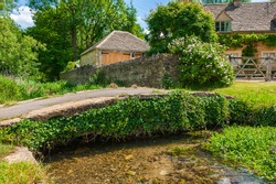 An arch stone footbridge over the River Eye in small picturesque village of Upper Slaughter in Cotswolds, England.