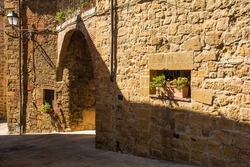 An arched passageway in a quiet residential road in the historic centre of the medieval town of Monticchiello near Pienza in Siena Province, Tuscany, Italy
