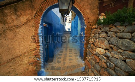 An arched passageway separating two ancient streets with sandy and blue walls #1537715915