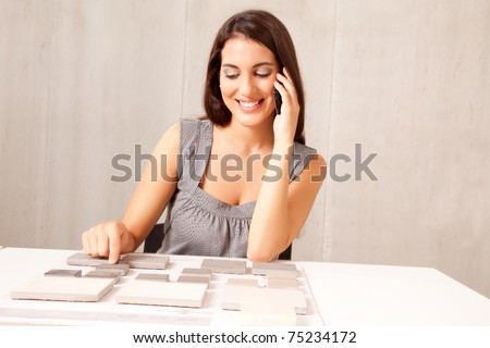 An architect / designer talking on the phone choosing a stone tile