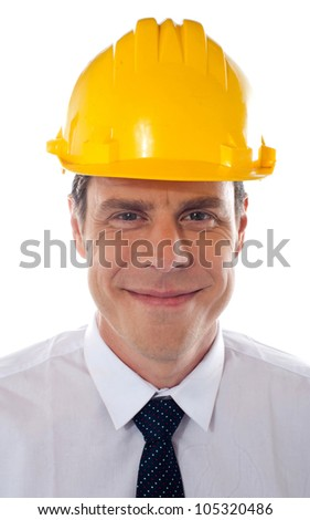 An architect wearing yellow safety helmet looking confidently at camera