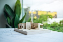 An architecture model with shop drawing paper on table in office with blur nature background