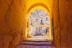 An archway in Matera shot in summer 2017 in the Sassi in south east Italy in Puglia. The stone steps lead up to some residential houses and the camera captures a beautiful golden light on the arch.