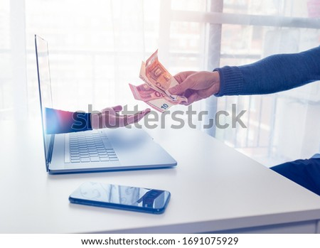 An arm comes out of a laptop to extort money from a person in front Foto stock ©