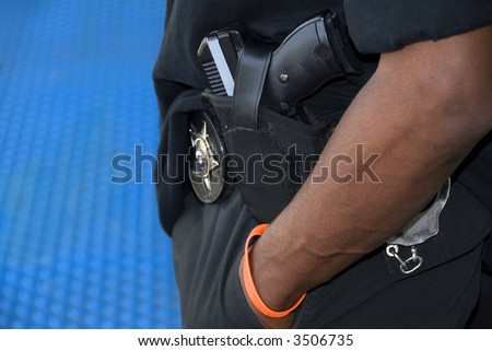 An armed patrolman stands on a platform in a North American transit station.