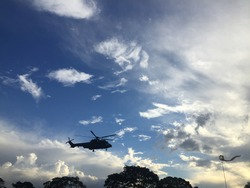 An army helicopter, at the height of the trees, the biruta, which shows the position of the wind, the image of nature in the blue sky of dusk with dark clouds, white and gray, setting sun.