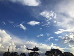 An army helicopter, at the height of trees, the image of nature at dusk in the city of Goiania, blue sky with dark, white and gray clouds, trees dark by the setting sun.
