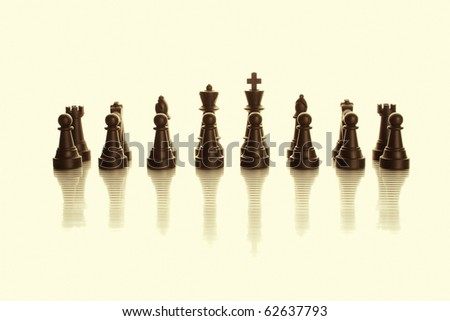 An army of black chess pieces. Yellow tint