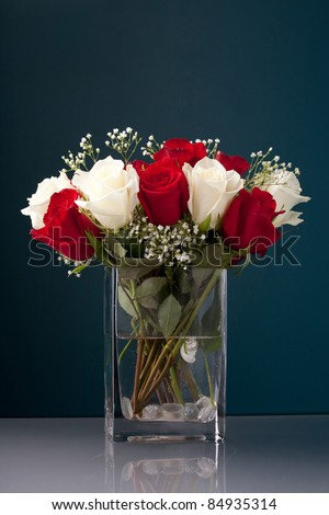 An arrangement of beautiful red and white roses with baby's breath in a clear glass vase.
