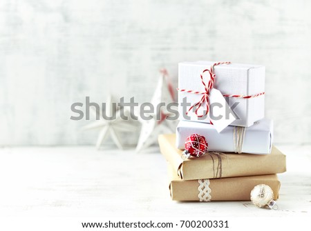 An Arrangement of Christmas Presents wrapped in gift paper in natural shades.  Symbolic image. Christmas background. Bright wooden background. Copy space.