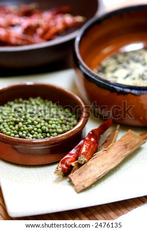 An arrangement of cooking ingredients. Dry chilis, wild rice, green bean and cinnamon sticks.
